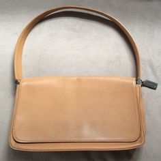"""Genuine COACH Tan Leather Bag - very used! Genuine COACH tan leather bag, which has been used often - there is wear/discoloration on the bottom (see second photo), minor discoloration on the bottom of the front flap (see first photo), and a small scratch on the right side, with a small black marking on the back (see third photo). There is one pocket inside, and one in the back. Approximately 12"""" long, 2 and 1/2"""" wide, and 7 inches high. Coach Bags Shoulder Bags"""
