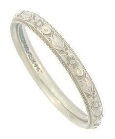 Intricately engraved details bring the floral design of this aantique wedding band to life. The blossoms on the face of this ring appear to float above a darkened surface. The edges of the band are trimmed in a delicate milgrain decoration. This romantic ring is crafted of 18K white gold and measures 2.79 mm in width. Circa: 1920. Size 7 3/4. We can re-size slightly.