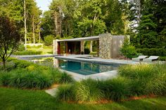 pool house with glass at front and back - made from natural materials (stone or shingle)