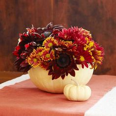 White pumpkins contrast with dahlias, sunflowers, and zinnias in this arrangement. Find more ideas for fall centerpieces: www.bhg.com/thanksgiving/indoor-decorating/centerpiece-and-tabletop-decoration-ideas-fall/?socsrc=bhgpin100512pumpkinflowerarrangement#page=15
