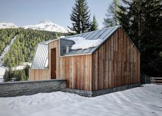 A timber guest house with an angular zinc roof has been added to a villa in an Italian ski resort.