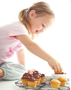 Giada's daughter Jade dips Mini Pumpkin Cupcakes with Chocolate Frosting from Weeknights with Giada by Giada De Laurentiis