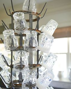 Blazona's other priority? Showing off her collections—finds she's amassed for years. Come April, this means birds' nests, milk glass, hotelware trays, and more. Between seasons, Blazona stores the treasures in plastic bins stacked floor-to-ceiling in the barn.  In this photo: A bottle-drying rack keeps Anthropologie glasses within easy reach on the kitchen island.