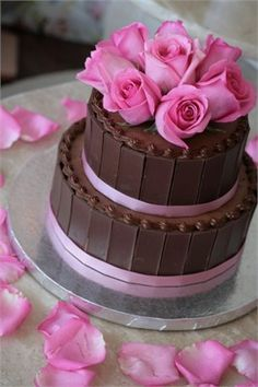 Chocolate brown wedding cake with pink decoration.
