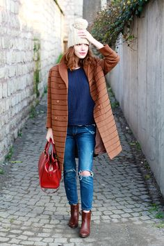 great layered style inspiration - navy sweater, camel coat, distressed jeans, and gorgeous leather booties