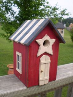 This is a fun Americana birdhouse for your patriotic birds! One of my favorite designs. I put a little door and windows, and a primitive star on this one. It is rustic red, antique white, and navy blue, and is time worn and stained. The bottom can be removed for cleaning Size-9
