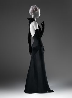 In the postwar period James was increasingly drawn to the muted sophistication of contrasting materials of differing luster. In this evening dress's monochromatic duet of blacks, the dull sheen of jersey juxtaposes with the high shine of satin