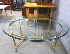 Oval brass and glass Hollywood Regency cocktail table. $395