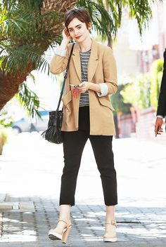 Lily Collins wears an oversized camel peacoat, black trousers and a black striped crop tee.