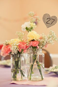 sparkly heart signs on sticks stuck in with the flowers. not necessarily just for table numbers, could put anything on there