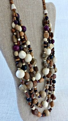 This necklace made of colorful different shapes of wooden beads : blocks , ovals , flat squares, round . Colors are : beige, off white , light