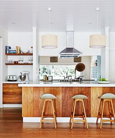 """opening to back room? The kitchen has a mid-century look, with Erik Buch stools from [Great Dane Furniture](http://www.greatdanefurniture.com/ target=""""_blank""""). Drawers, panelling and flooring are all American oak."""