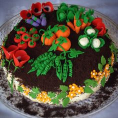 Garden Cake by Anna's Cooking Diary. Cheese cake topped with strawberries covered with whipped cream toped with crushed chocolate filled oreo cookies decorated with handmade gum paste vegetables and flowers.
