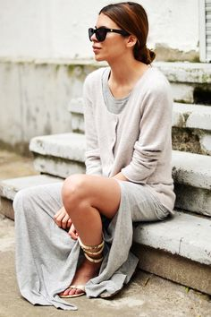 Maja Wyh of Maja Wyh in a grey dress, sweater, and strappy sandals