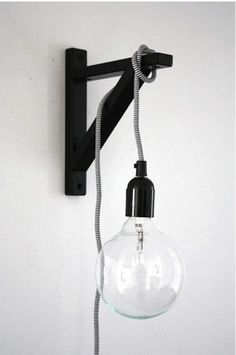 For a space-saving lamp, hang a lightbulb on a cord off of a wall-mounted shelf bracket.: