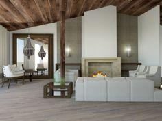Salón abuhardillado con techo de madera y chimenea