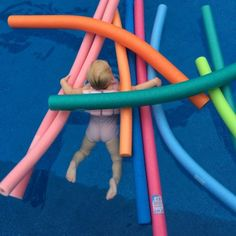 baby swimming with pool noodles