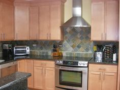 Multi-colored slate backsplash, Ubatuba granite counter, natural maple cabinets