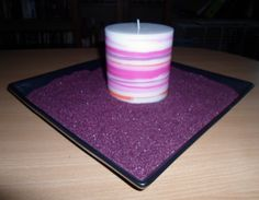 Decoration with purple sand and a striped candle.