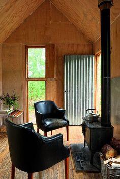 petit salon en bois avec devant un poêle à bois des fauteuils en cuir noir vintage Knoll