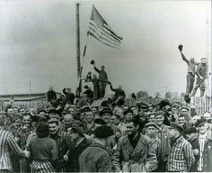 Former prisoners liberated from the Dachau Concentration Camp cheer at the raising of the Stars and Stripes, April 1945.