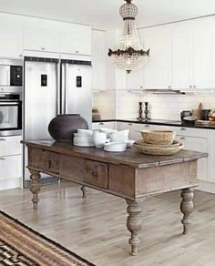 This antique island in the kitchen adds a unique rustic farmhouse charm to the space.