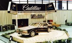 """1980 Chicago Auto Show - An all-new Seville sedan, sitting on a raised platform, dominates this scene at Cadillac's exhibit space. Billed as """"quite possibly the most distinctive car in the world today,"""" the restyled Seville featured a """"bustleback"""" profile with a humped trunk lid. This example has two-tone paint and a sunroof. A diesel engine was standard, with gasoline V-8 an option. The back half of an Eldorado coupe can be seen behind the Seville."""