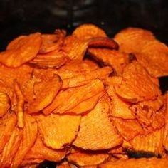 A sweet and spicy snack made with cayenne pepper, maple syrup, olive oil, and sliced sweet potatoes.
