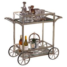 Bar cart with a glass top and iron frame.  Product: Bar cartConstruction Material: Glass and ironCol...