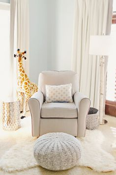 Off-white nursery with giant stuffed giraffe behind rocking chair