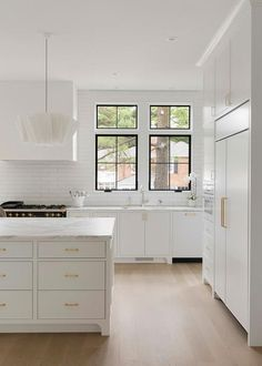 Stacked white flat front doors fitted with brass pulls accent a kitchen island topped with a white and gray marble countertop lit by modern white chandeliers. Source by thesmithhotel Apartment Therapy, Kitchen Interior, Kitchen Design, Layout Design, Ikea, Kitchen Trends, Kitchen Ideas, Transitional Kitchen, White Contemporary Kitchen