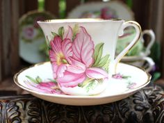 A delightful Regency Teacup and Saucer - Pink Orchids on a crisp white background. English bone china.A wonderful addition to any afternoon tea party, this set is sure to delight!Standard sized teacup and saucer with no damage noted and all gilded rims are 100% intact.