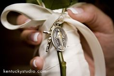 If you and your groom have a favorite saint, you might want to add that saint's medal to your bouquet. If you can't decide on a saint, adding a rosary to your bouquet is also very beautiful.