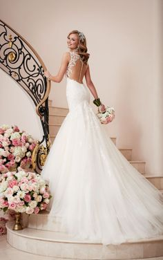 This designer fit and flare wedding dress from Stella York features a figure-flattering fitted bodice that flares just below the hips into a full tulle skirt. Sparkling beading throughout catches the eye, while the low-cut illusion back makes for an elegant exit. The back zips up with ease under fabric-covered buttons.