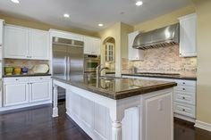 Classic kitchen beauty with white cabinetry, granite countertops and  island with breakfast bar.