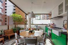 Varando do apartamento se transforma em cozinha gourmet com cara de varanda de casa graças aos bancos de madeira, plantas, painel ripado e a farta luz natural.