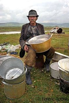 This old Karderár Gypsy is proudly showing his work.  In the distance you can see his tent and dog.  The pots are made out of scrap metal collected in the villages