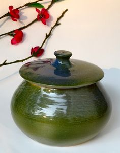 This small porcelain Japanese tea jar is ideal for anyone who appreciates stylish decor with an Asian flair! A shimmery green/blue glaze adorns this delicate Asian inspired porcelain vase. Use it for keepsakes, loose tea, candies, sugar or as just a beautiful piece on your mantle.