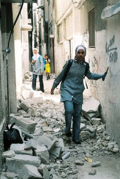A Palestinian girl attending a UNRWA school side-steps the rubble of a damaged home