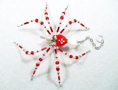 Amore  This beautiful spider is hand-beaded with white glass pearl beads and red and white pearl seed beads. Her abdomen is made with red and