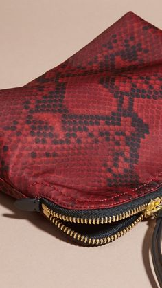 A printed durable Burberry pouch reflecting the patterns of the runway. The pliable shape has a zip-top closure with a practical leather zip pull. The versatile piece works as a beauty bag or clutch, with protective lining lending a functional edge.
