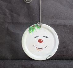 This is a hand painted, metal Mason jar lid, Christmas tree ornament with a snowman face. It measures 2-3/4 in diameter and has a 3 wire hanger. These