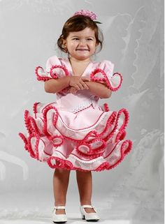 Trajes de flamenca de niña 2015 corto Carmín de color beige con madroñeras de color turquesa en volantes, son vestidos de flamenca con talle alto con subida lateral, tiene tres volantes y las mangas a media manga con un volante, el cuello tiene forma de pico. #trajesdeflamencaniña #trajesdeflamenca2015 http://www.elrocio.es/trajes-de-flamenca-nina/1660-trajes-flamenca-nina-carmin.html