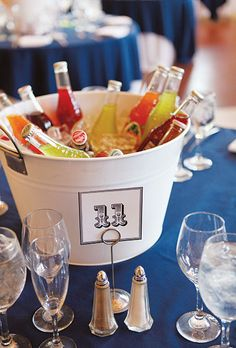 """Brides: Carnival Themed Printed Table Numbers. White beverage tubs from Target were filled with Jarritos sodas and Cheerwine, and used as centerpieces. """"The sodas added a pop of color on each table, plus they were useful and cost-friendly,"""" says Kathleen. """"We also had twisty straws for the kids, which they loved."""""""
