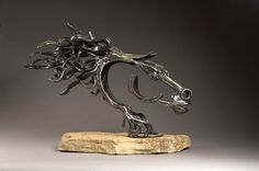Traditional blacksmith forged reclaimed steel including horseshoes on a stone base.: