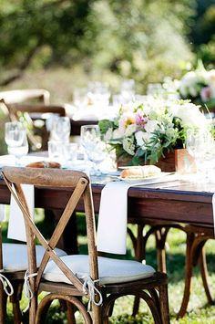 Simple wooden reception tables with lush, boxed centerpieces | @angiesilvy | Brides.com