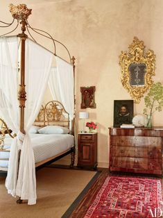 A romantic guest room in this 16th-century country home in Toledo, Spain, contains a 19th-century brass bed and gilded mirror, which both once belonged to the wife of a king