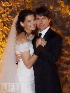 Tom Cruise and Katie Holmes Tie the Knot  Tom Cruise and Katie Holmes take their official wedding photo on Nov. 18, 2006. Holmes wore an off-the-shoulder Armani gown with an ivory silk train adorned in Valenciennes lace and Swarovski-beaded crystal embroidery.