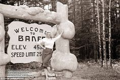 Marilyn Munroe looks stylish in cream top and pencil skirt as she poses by the Banff sign in the Canadian Rockies