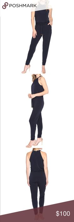 MICHAEL KORS Studded Halter Jumpsuit (Navy Blue) So sleek, this one-piece look from MICHAEL Michael Kors®. Is a great way to redefine your wardrobe. Add a blazer for the workweek or accessories for a night out.  * Stretchy polyester fabrication offers a flattering fit. * Stud embellishments at halter neckline. * Ruching detail at neck creates a gentle drape. * Sleeveless design. * Concealed back zipper closure. * Elastic waistline with removable self-tie belt. * Side hand pockets. * Tapered…